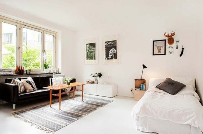 posters and other decorations, inside room with white walls and floor, simple single bed, black sofa and wooden coffee table, studio apartment decorating ideas, striped gray rug and cushions