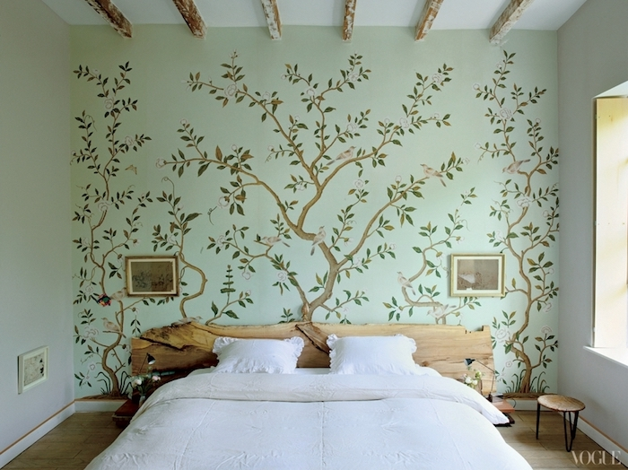 antique-style mural, with thin blossoming trees, with green leaves, and small gray birds, in bedroom with wooden ceiling beams, double bed with headboard, made from a piece of natural wood