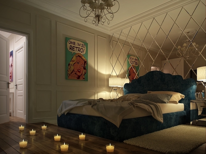 eight small lit candles, on a wooden floor, near blue bed with soft headboard, one wall features white paneling and pop art poster, the other is covered by mirror in diamond shapes
