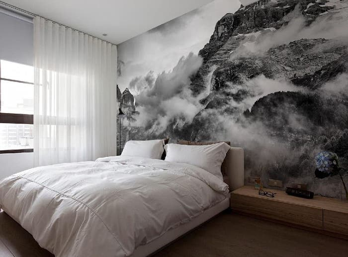 large wall art, grayscale photo wallpaper depicting cloudy mountains, near bed with fluffy white duvet, and two matching pillows, wooden cupboard and window