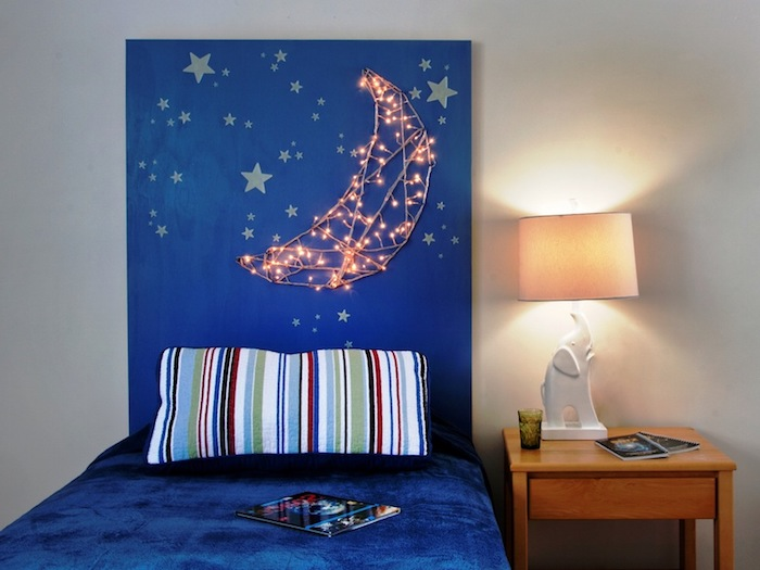 string lights attached to a blue board, forming a glowing moon shape, pale yellow star shapes, bedroom wall decor, single bed with blue velvety bedding, and a striped pillow