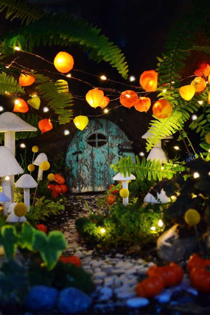 lanterns and tiny string lights, inside a night-time fairy garden, white mushroom figurines, pebbled path and various green plants, miniature teal-colored shabby door