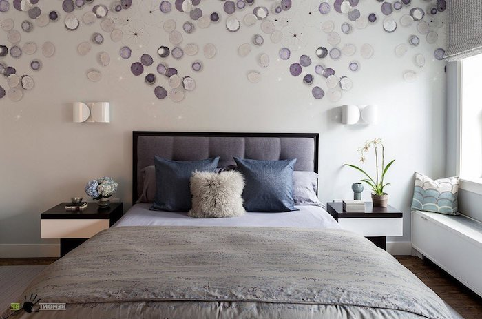 many round off-white and purple decorations, on a wall behind a double bed, bedroom decorating ideas, cushions and covers in different shades of gray