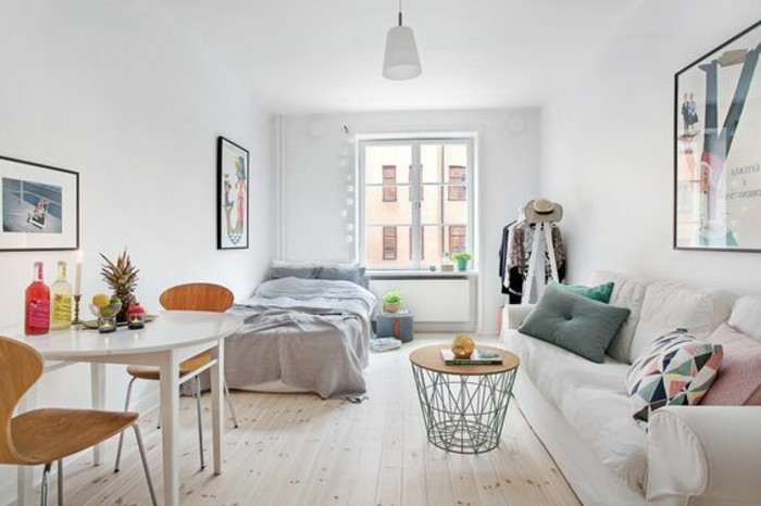 minimalist one-room accommodation, with white sofa, modern coffee table made from metal and wood, studio apartment decorating ideas, bed with pale gray cover
