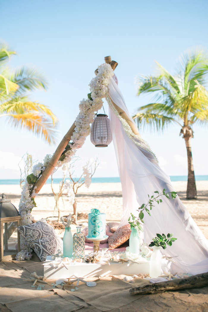 tent in boho style, decorated with flower garlands, lanterns cushions and bottles, on a sandy shore, near the sea, beach wedding venues, palm trees in the background