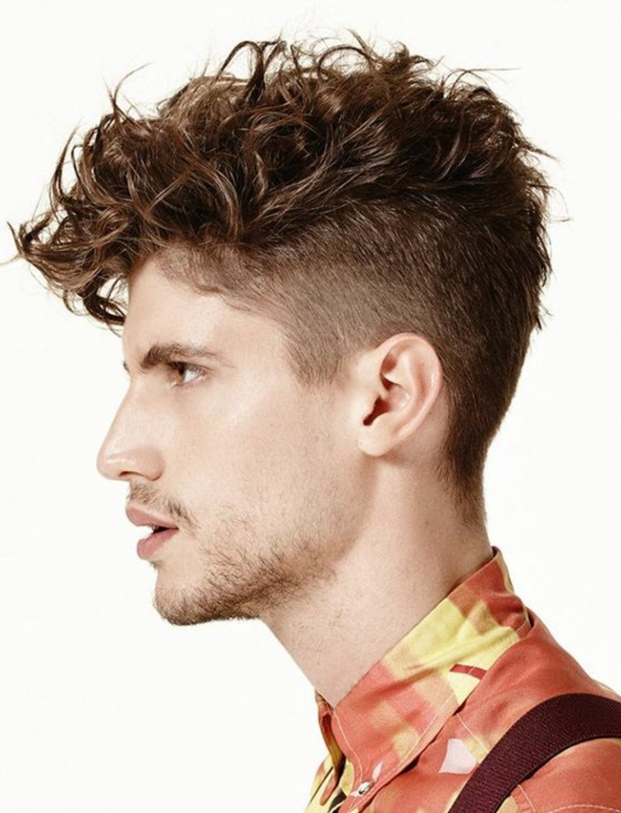 quiff on a brunette man, with very short beard and a mustache, curly haircuts, patterned shirt in orange and yellow