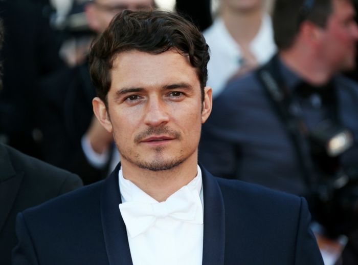 short curly hair, worn by Orlando Bloom, in white formal shirt, matching bowtie and black tuxedo, short beard and mustache