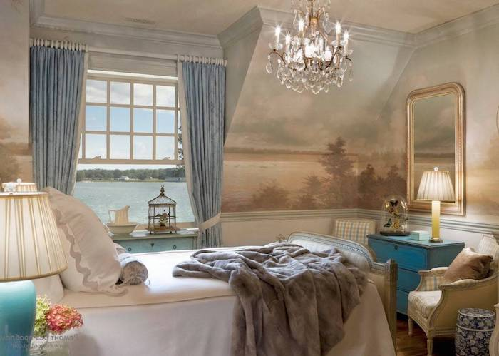 vintage style room, with pastel colored landscape mural, in pale blue and brown, bedroom decorating ideas, retro furniture and a crystal chandelier