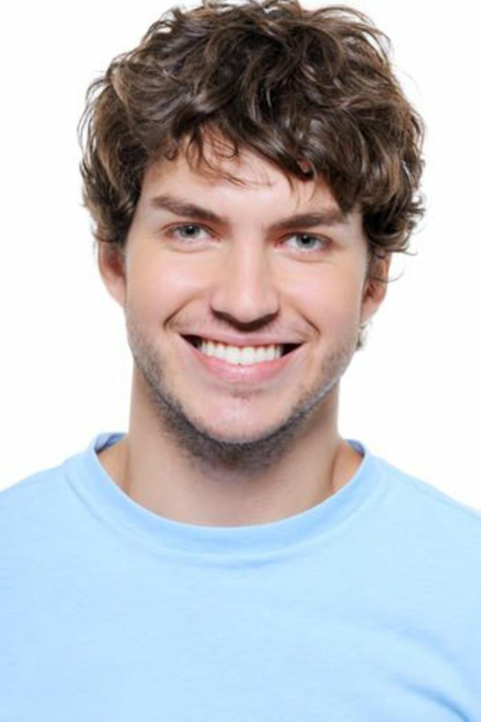 tousled curly hairstyle, on smiling brunette man, dressed in a pale blue t-shirt, and smiling widely, stubble on his lip and chin