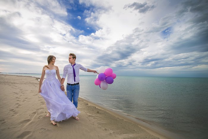 pale purple sleeveless wedding gown, worn by young smiling bride, holding hands with a groom in a matching shirt, and a dark purple tie, combined with jeans, beach weddings in florida, sandy shore and sea