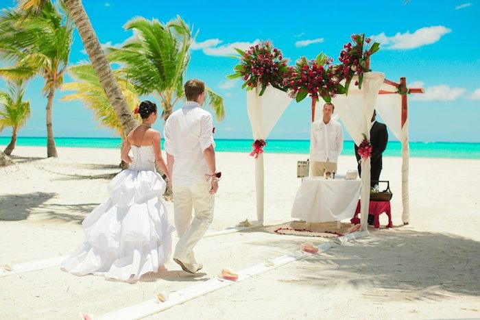 bali nuptials ceremony, white sandy beach, azure sea and blue sky, couple walking towards an altar, decorated with white fabric and flowers, beach wedding venues, palm trees swaying in the wind