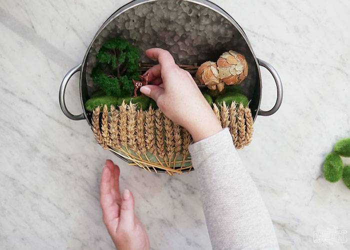miniature deer figurine, placed near a tiny tree, small wooden fence, and 2 dried mushrooms, by two female hands, fairy garden with wheat stalks, inside metal cooking pot