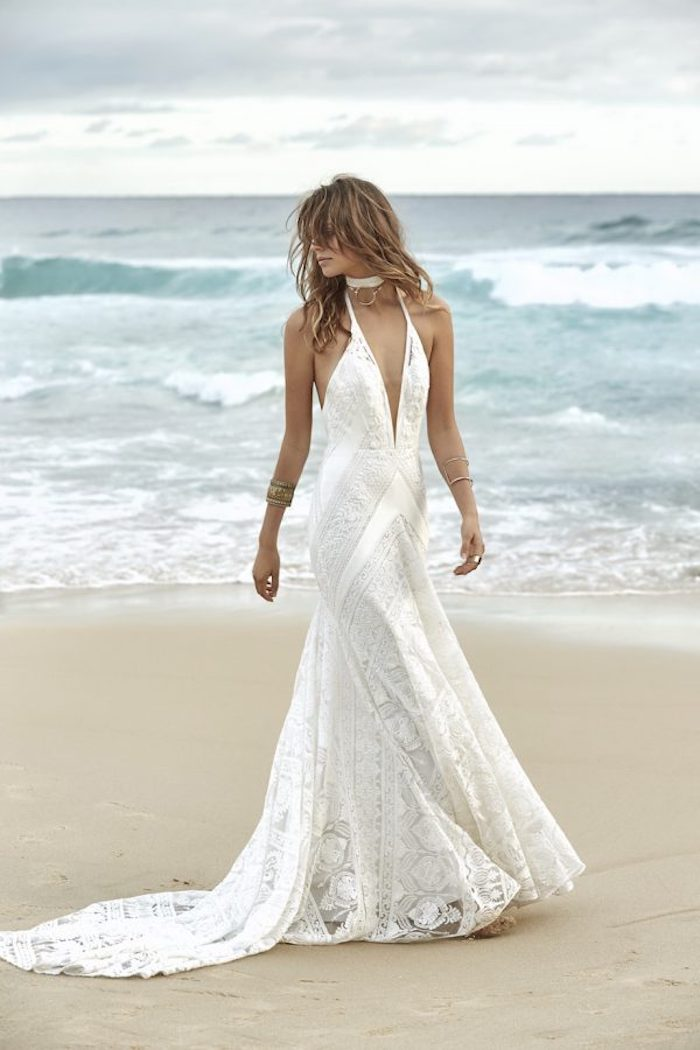 tousled light brunette hair with bangs, on tanned model in white lace beach wedding dress, with plunging neckline, standing on a sandy sea shore
