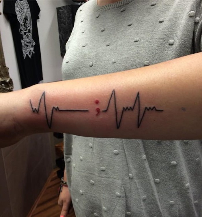 lifeline tattoo in black, punctuated by a small red semicolon, on the side of a person's lower arm, ideas for the semicolon project