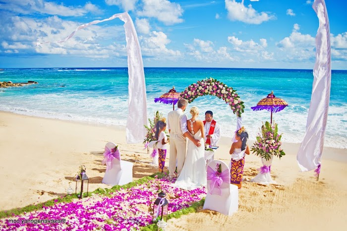 colorful wedding ceremony, on a beach with fine, pale yellow sand, and azure blue sea, purple and white flowers, decorating the aisle and the wedding arch, couple standing in front of a minister