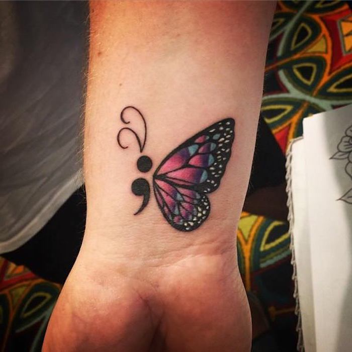 butterfly tattoo inspired by the semicolon project, with thick black outlines, a semicolon body, and wings decorated with purple, blue and white, on a person's wrist