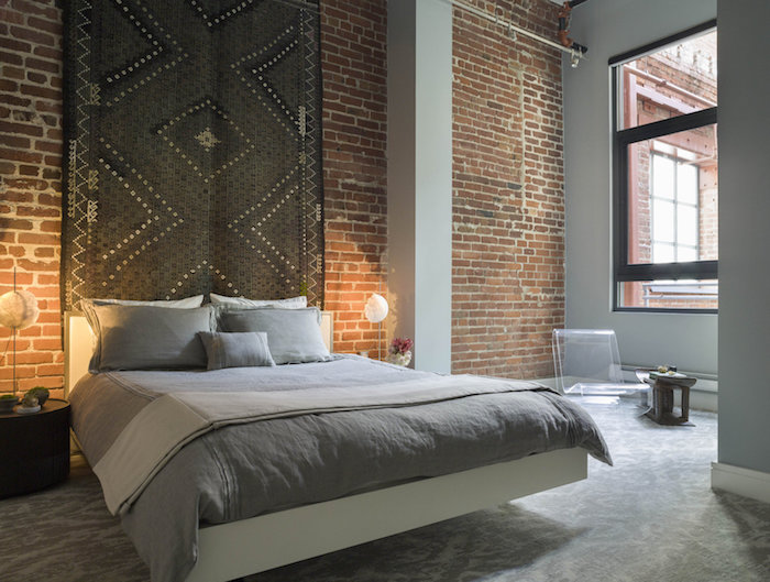 big dark gray rectangular rug, with white and black details, hanging on a brick wall, over a double bed, with grey pillows and covers, bedroom design, industrial style room