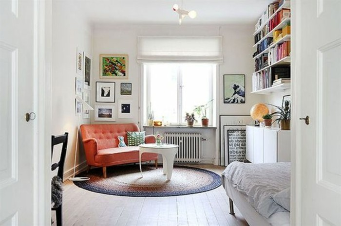 rusty red settee, near modern white coffee table, placed over round multicolored rug, retro-style apartment design