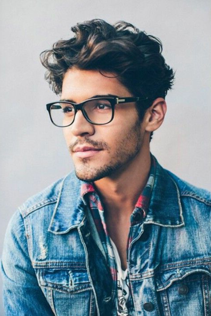 plaid shirt worn over a t-shirt, with a retro-style, ripped denim jacket, on man with brunette hair, styled in messy curls, hairstyles for short curly hair, stubble and glasses