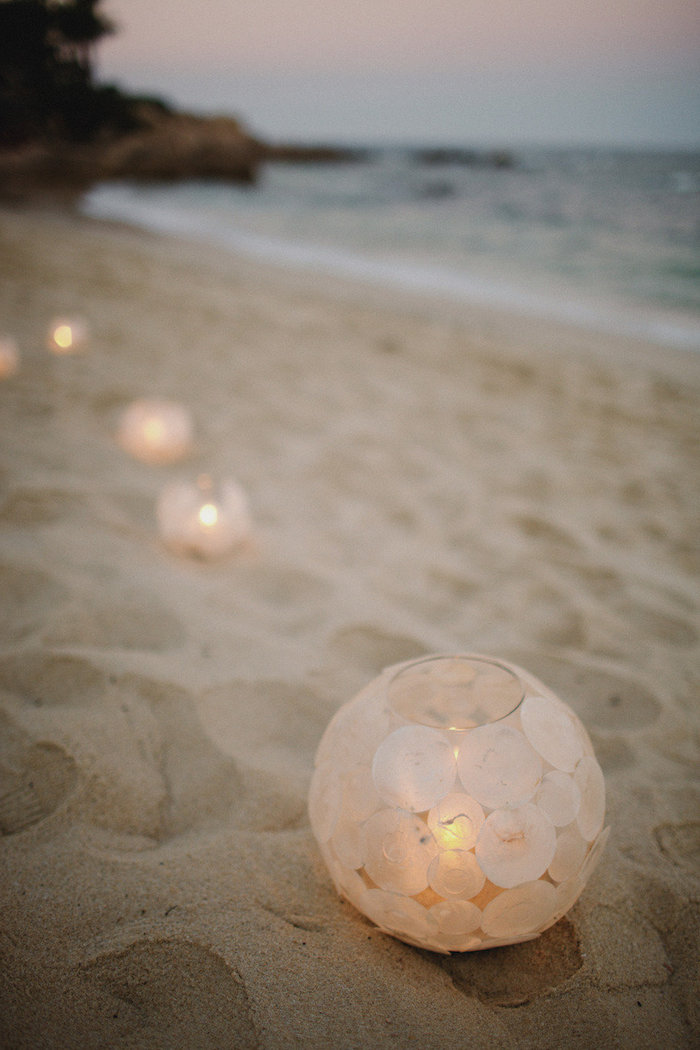 several round glass lanterns, decorated with circles of cream-colored rice paper, containing lit candles, placed on fine beige sand, near the sea