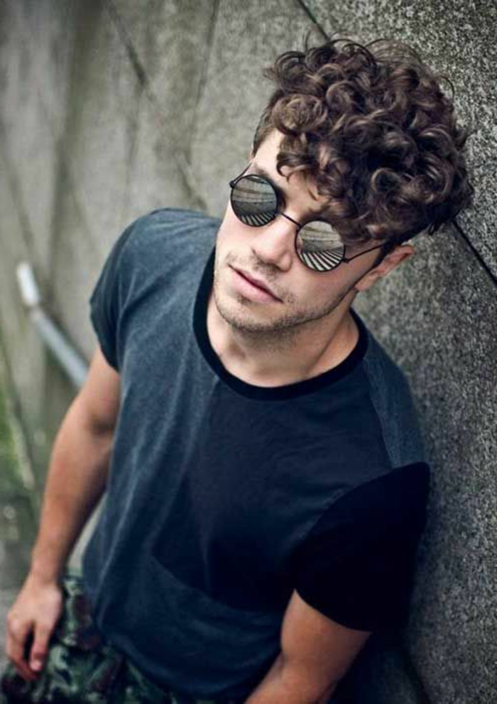 young man with curly brunette hair, wearing round reflective sunglasses, and a grey t-shirt, curly hairstyles, he is leaning on a gray wall