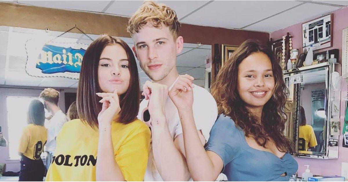 alisha boe standing next to tommy dorfman, and selena gomez, all showing their arms with identical, small black semicolon tattoo designs