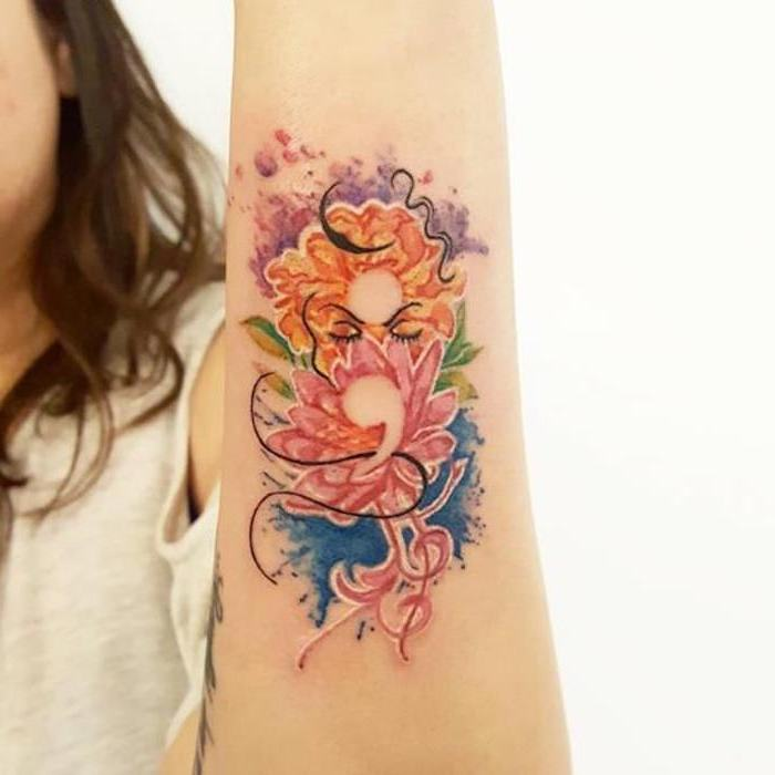 elaborate floral tattoo, in orange and pink, blue and green, purple and black, with subtle semicolon tattoo hidden within, on a woman's arm