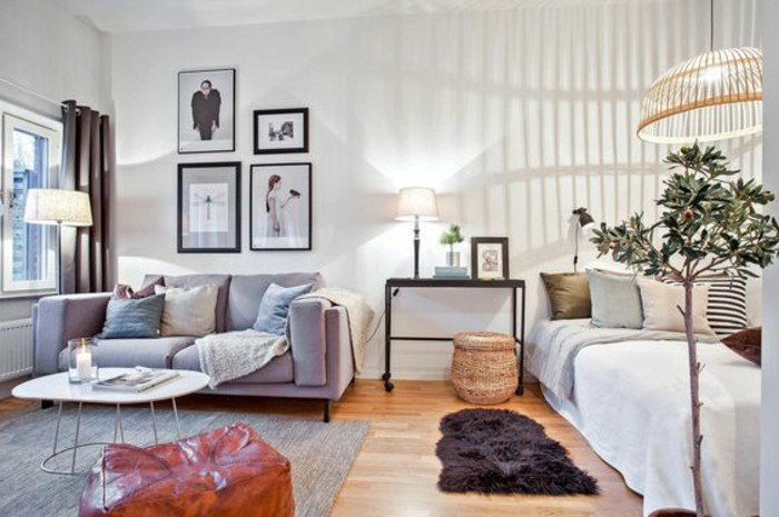 three lit lamps, inside a room with white walls, studio apartment ideas, gray sofa and bed with many cushions, laminate floor with rugs, framed artworks and a coffee table