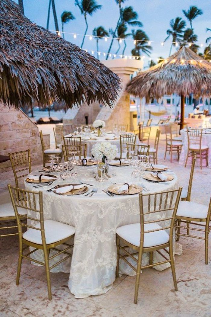 straw-covered sun umbrellas, near several round tables, set for dinner, with lace tablecloths, and gold and white chairs, on a beach with tall palm trees