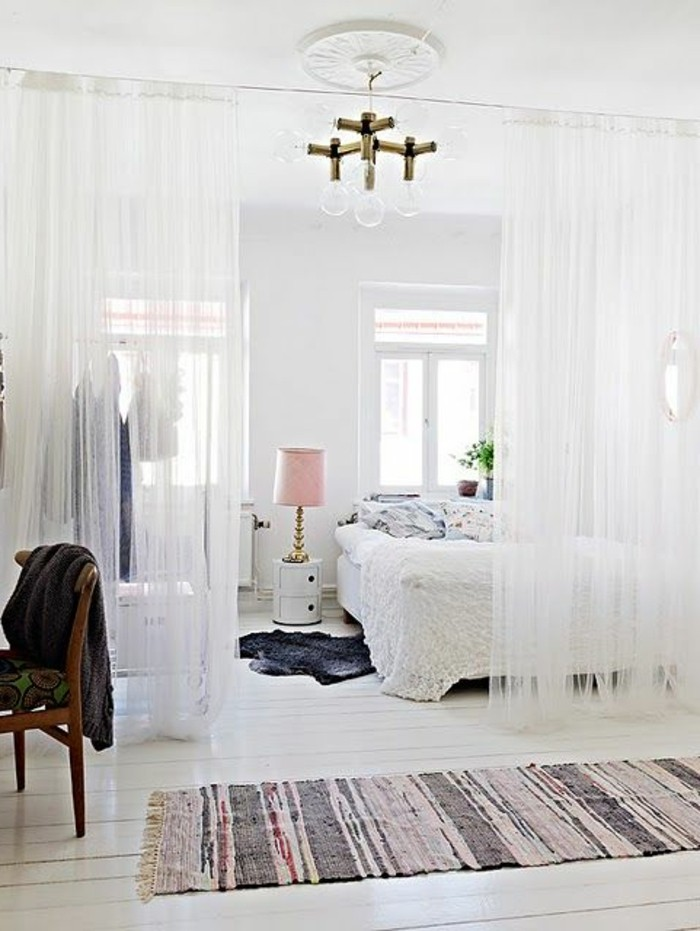 half-drawn curtains, made from sheer-white fabric, separating a sleeping area with white bed, how to decorate a studio apartment, ivory-colored wooden floorboards, vintage chair and rug