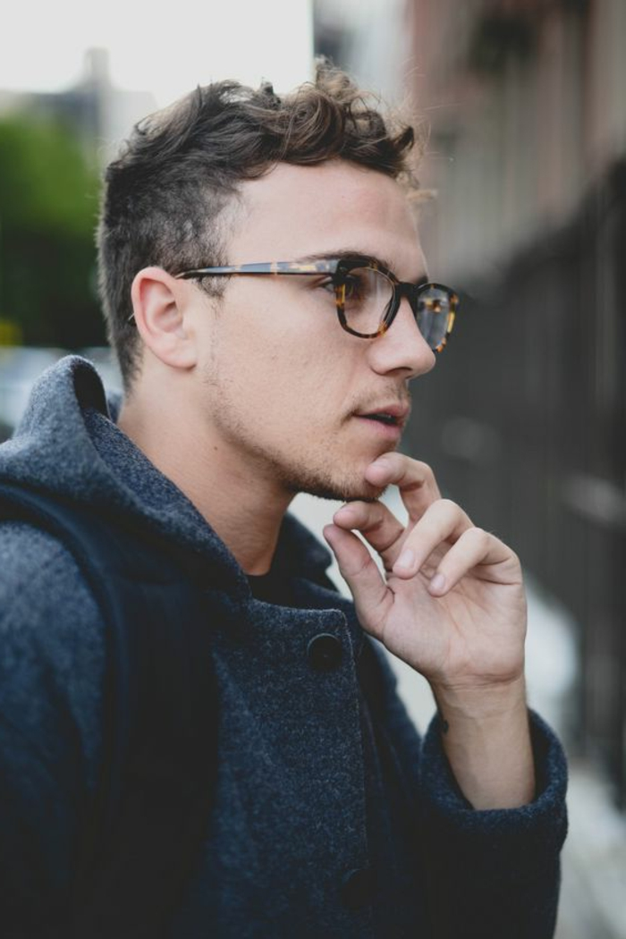 glasses worn by young man, with short curly hair, wearing grey hooded woollen coat, and looking thoughtful, stubble on chin and lip