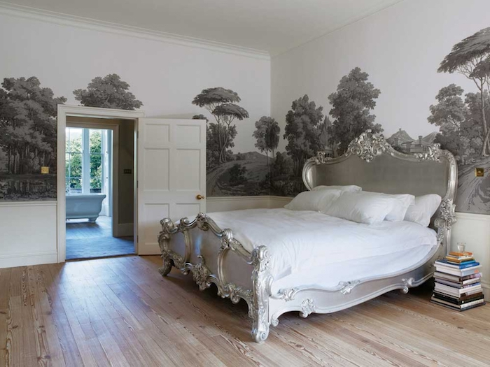 grayscale mural depicting countryside with trees, inside a room with light laminate floor, and a bed with silver baroque style frame, wall art décor in an antique style