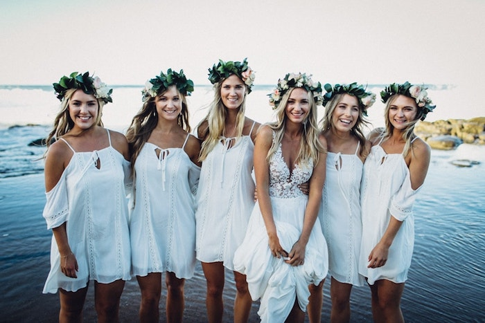 five bridesmaids wearing short, white boho dresses, with cold-shoulder details, and leafy green flower crowns, near a bride with embroidered floaty gown, wedding dresses for beach wedding, sea in the background