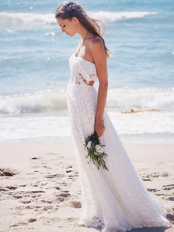 sleeveless white gown, with lace and cutout details, casual beach wedding dresses, worn by young brunette woman, with a single side-braid, holding bouquet of white flowers