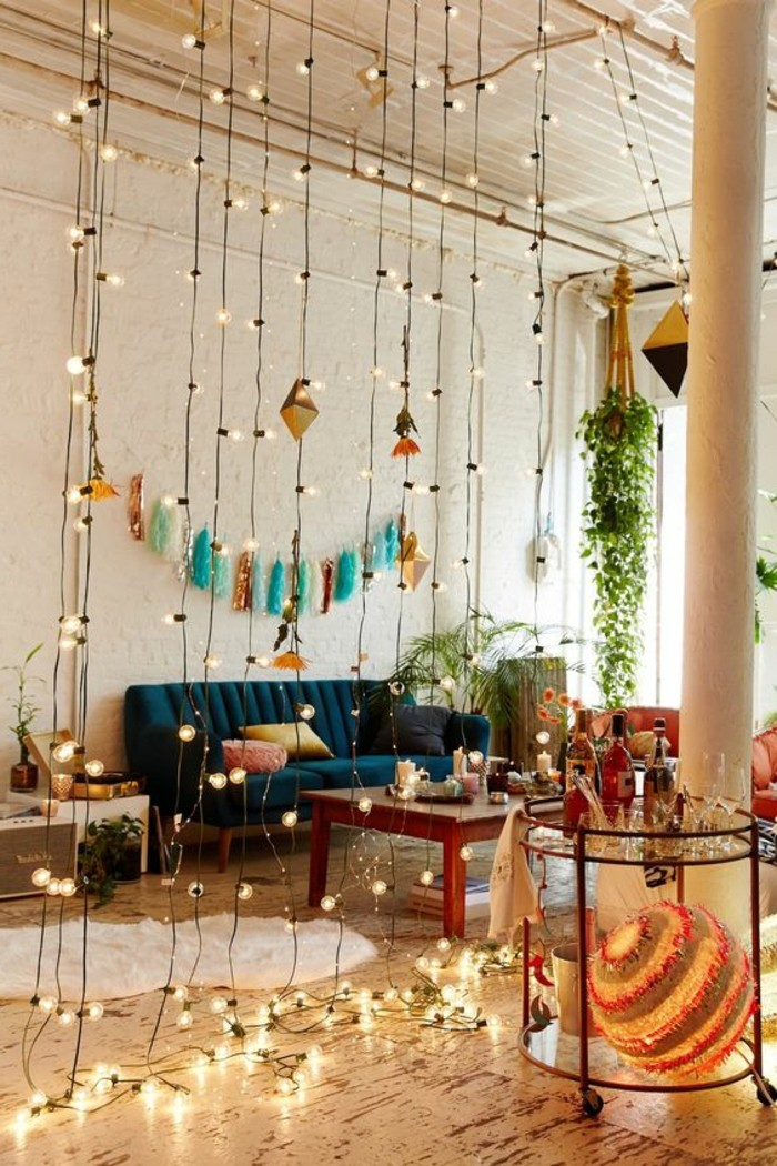 curtain made from lit string lights, inside studio with dark blue sofa, and wooden coffee table, small apartment living room ideas, several potted plants and colorful decorations