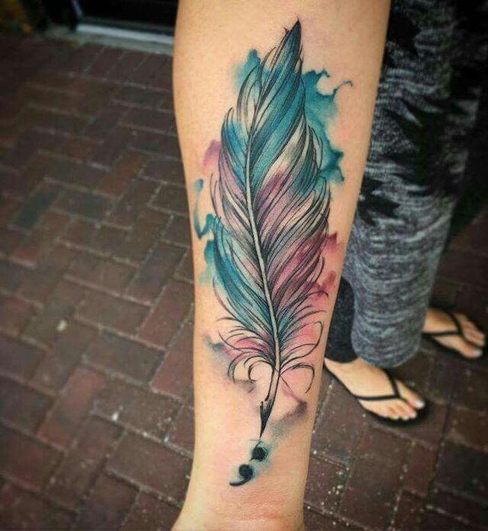 feather quill tattoo with black outlines, and blue and pink watercolor effect, near small black semicolon tattoo, on a woman's hand and wrist