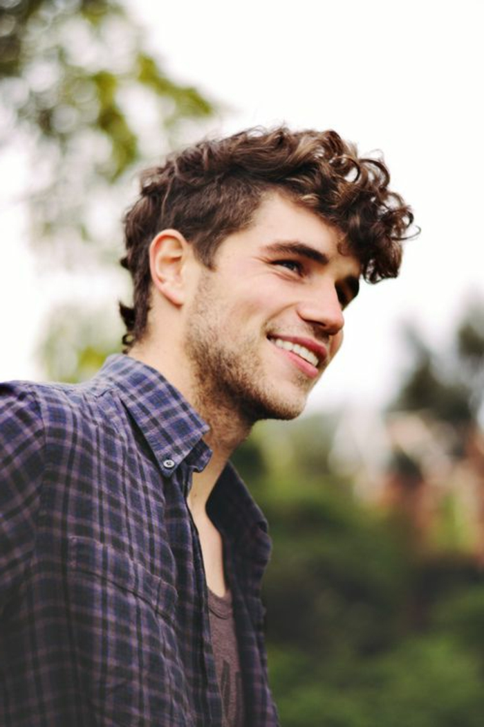 happy young man, with curly hair, left longer on top, and kept shorter at the sides, wearing a violet plaid shirt, over a purple t-shirt, curly haircuts