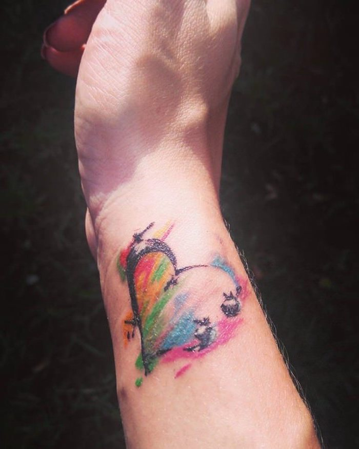 heart tattoo in a smudged, watercolor-like style, decorated with rainbow colors, subtle semicolon project tattoo, on the side of a person's wrist