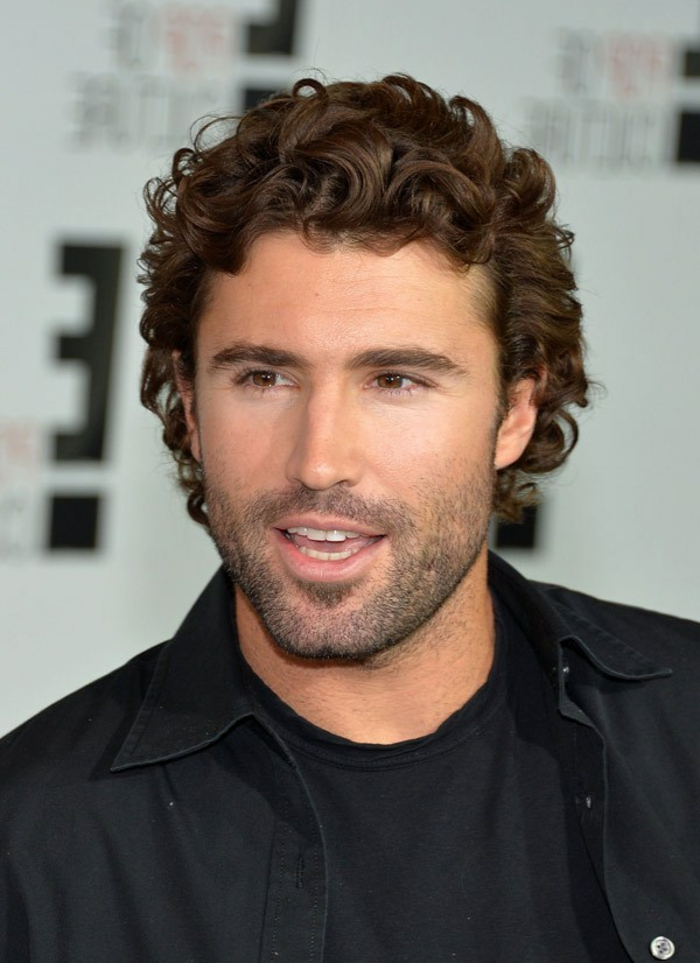 talking man with stubble on his lower face, soft warm brown curls, guys with curly hair, black shirt worn over a black t-shirt