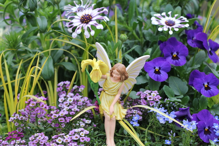 fairy garden ideas, little fairy statuette, with yellow dress, and white wings, holding a yellow flower, in garden with pansies and other purple flowers