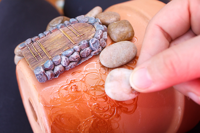 hand sticking a small pale pebble, to an orange ceramic pot, decorated with a tiny painted clay door, fairy garden ideas, beige and brown pebbles