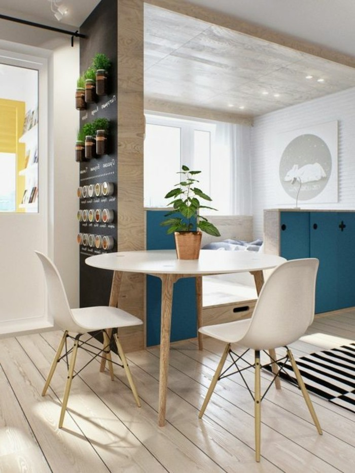 set of modern round table and two chairs, wooden laminate floor, cool apartment design, partial wall decorated with various potted plants