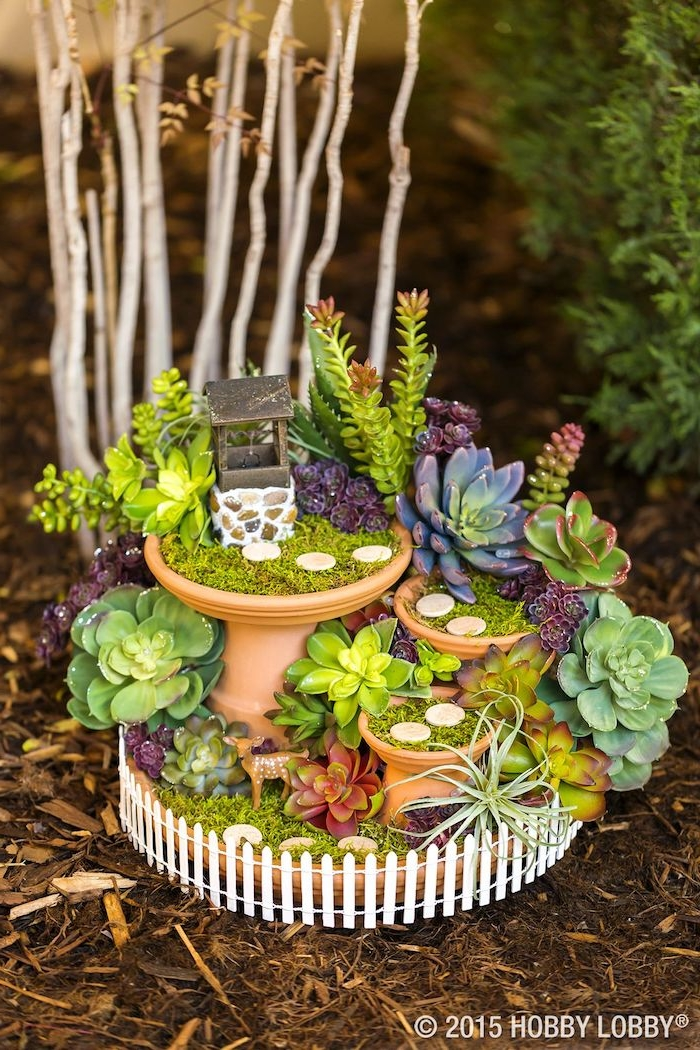 succulent fairy garden, inside several ceramic dishes, decorated with green moss, tiny round tiles, and a miniature water well