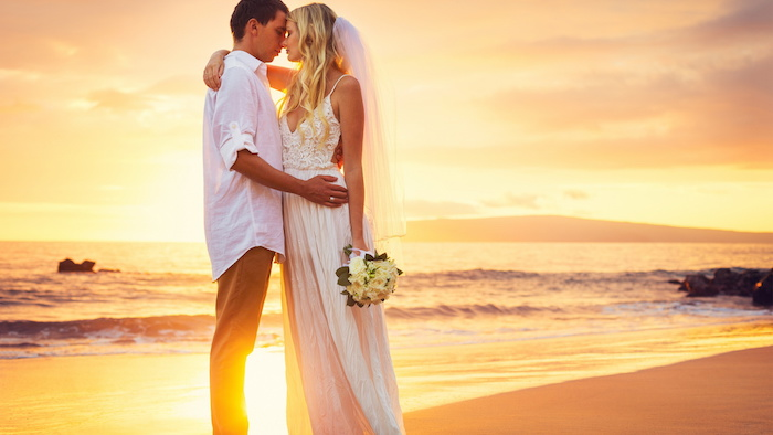 beach wedding, bride in long white boho dress and veil, hugging groom in white shirt, and beige pants, near the sea at sunset