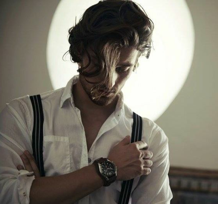 strand of hair, falling over a man's face, guys with curly hair, white shirt and suspenders, large wrist watch, stubble on chin