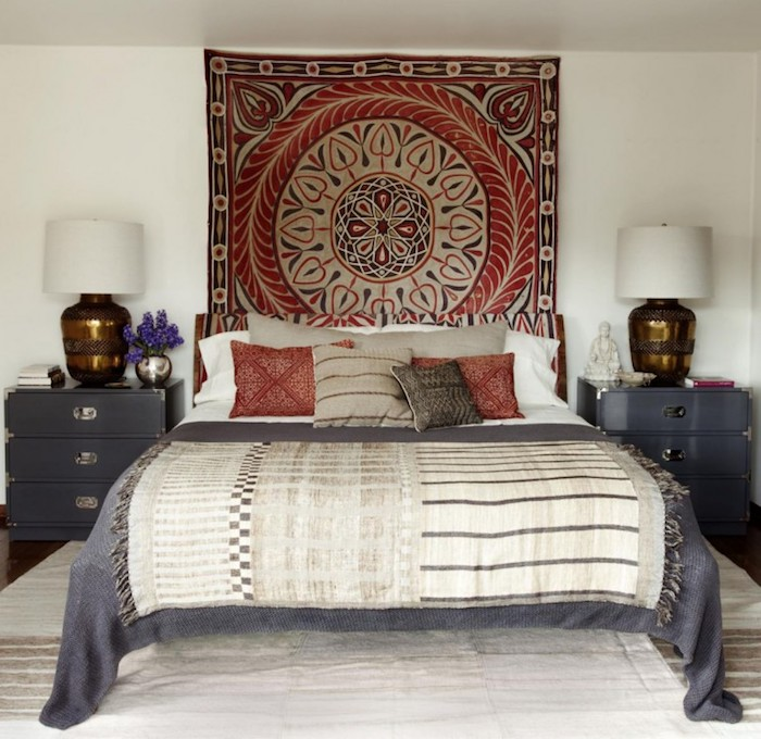 mandala in red, dark gray and pale beige, on a square rug, hanging over a bed in matching colors, bedroom design, two identical gray bedside cupboards