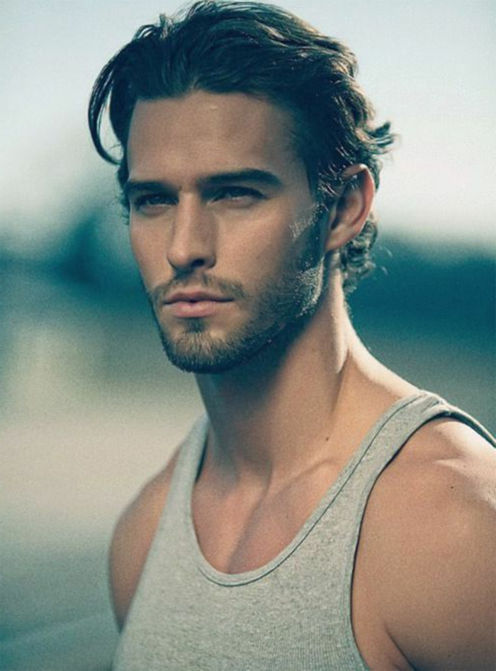 slicked back wavy dark hair, on man with very short beard and mustache, haircuts for men with curly hair, light grey top