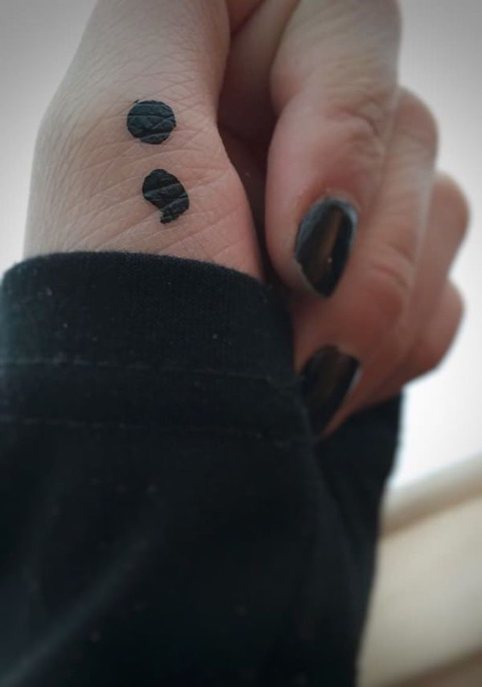 hand-painted temporary tattoo, done with black marker, on a person's thumb, fingers with black nail polish, black jumper sleeve