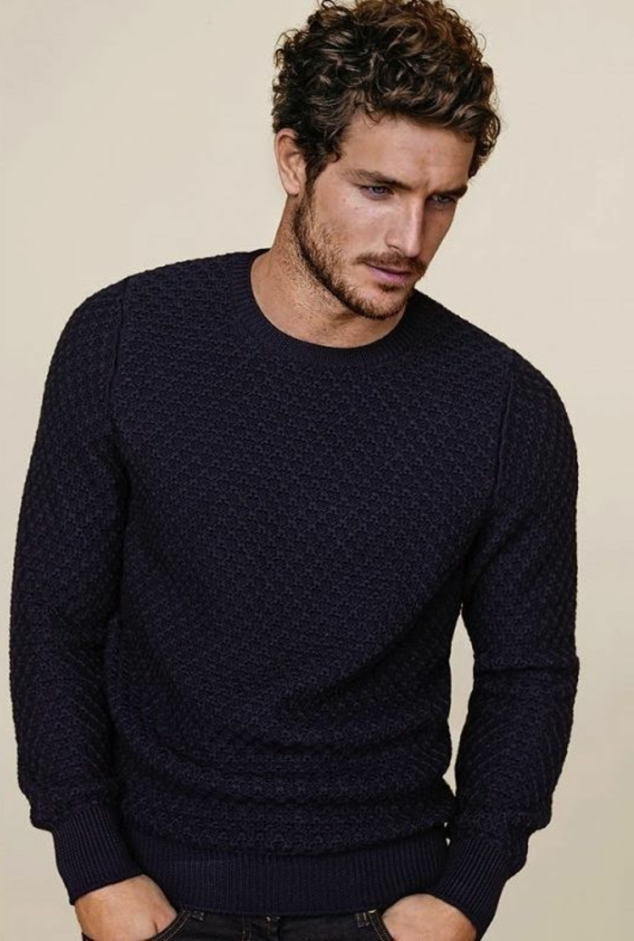 versatile haircut for curly men, worn by a brunette guy, in a textured dark blue knitted jumper, looking to one side, with hands in his pockets