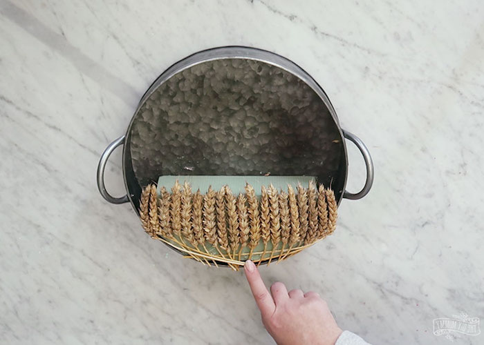sponge entirely covered in dried wheat stalks, stuck inside a metal cooking pot, spring forest wreath idea, fairy garden
